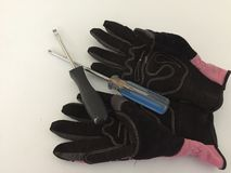 Work Gloves and Screwdrivers. Women`s work gloves and two different screwdrivers. One screwdriver is known as a phillip`s head screwdriver and the other is a stock photo
