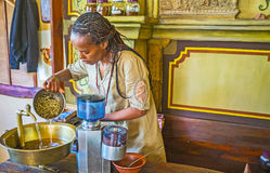 Work with green coffee beans. KIEV, UKRAINE - JUNE 4, 2017: Preparing for coffee ceremony - Ethiopian Tigrayan woman washes green coffee beans before the roast Stock Photography