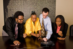 Work group on a conference call. A group of workers stand at a a conference room table during a conference call. All four team members gesture toward the phone Stock Photography