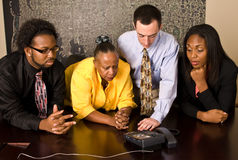 Work group on a conference call. A group of workers stand at a a conference room table during a conference call. All four team members look at the phone with a Stock Photography