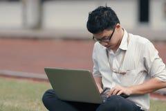 Work hard Asian business man using laptop on the green grass. stock photos