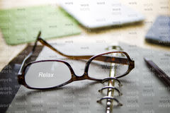 Work Hard, Blur Vision. Work hard, must relax. The glasses is on the notebook with a pen. A tablet and smartphone are in the background. The word `Relax` is on Stock Images
