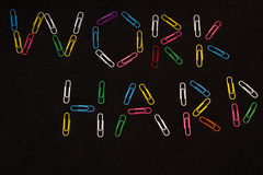 Work Hard. With Colourful Paper Clips on Black Background Royalty Free Stock Image