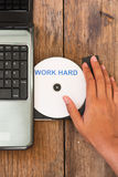 Work hard concept laptop with compact disk Royalty Free Stock Photography