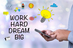 WORK HARD DREAM BIG. Person holding a smartphone on blurred cityscape background stock photos