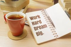 Work Hard Dream Big. Inspirational quote on notebook with pen, cup of tea and pile of books Royalty Free Stock Images