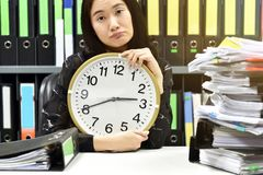 Work hard, Office worker holding a clock, Working overtime and lot of work royalty free stock photo