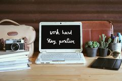Work hard Stay positive on computer screen with creative workplace. Work hard Stay positive Hand drawn lettering. Inspirational quote on computer screen with royalty free stock photo