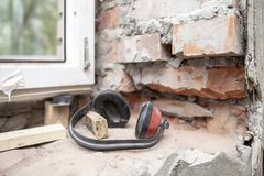 Work headphones protect against noise lying on a brick wall near the PVC window. Process of installing metal-plastic construction stock photos