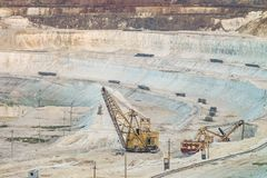 Work of heavy grapple excavators in a deep chalk quarry. Mining industry. Stock Photo