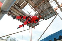 Work at height by rope access. Worker with red boiler suit work at height low down by rope access stock images