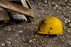 Work helmet. Dirty old work helmet left on the ground of construction site Royalty Free Stock Image