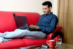 Work from home. Young relaxed man working on laptop at home Stock Photos