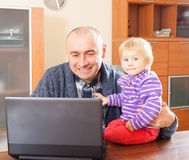 Work at home. Adult father and baby daughter royalty free stock photo