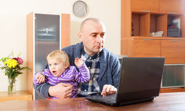 Work at home. Adult father and baby daughter royalty free stock images