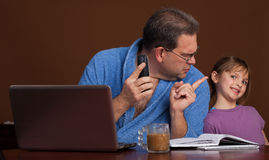 Work at home distraction. A father scolding his daughter for interrupting him while on a conference call stock image