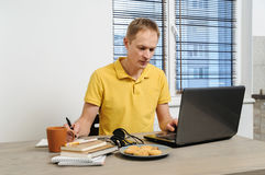 Work at home. The man sits at a table looking at the laptop screen Stock Images
