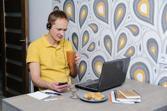 Work at home. The man sits at a table looking at the laptop screen Royalty Free Stock Photo