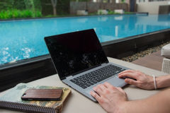 Work from home by the pool. Work from home on your laptop royalty free stock photo
