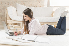 Work from home. Smiling young woman laying down on the floor typing on laptop, dressed in casual clothes. Online study Stock Photo