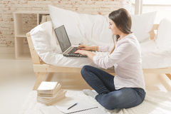 Work from home. Smiling young woman sitting cross legged on the floor typing on laptop, dressed in casual clothes. Online study Royalty Free Stock Images