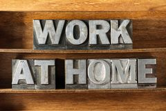 Work at home tray. Work at home phrase made from metallic letterpress type on wooden tray royalty free stock images