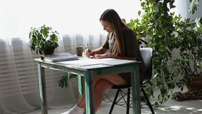 Work at home. young beautiful freelancer woman is working at the table by the window in the house. modern ecological. Interior with living plants stock footage