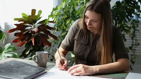 Work at home. young beautiful freelancer woman is working at the table by the window in the house. modern ecological. Interior with living plants stock video footage