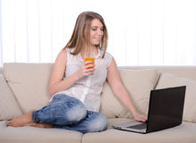 Work At Home. Young beautiful woman working with a laptop sitting on sofa at home stock photography