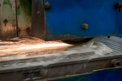 Work of an industrial surface grinding machine. Grinding of a flat metal part. Sparks fly out from under the grinding wheel. Grinding with a coolant Stock Images