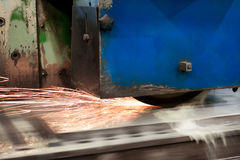 Work of an industrial surface grinding machine. Grinding of a flat metal part. Sparks fly out from under the grinding wheel. Grinding with a coolant Royalty Free Stock Photo