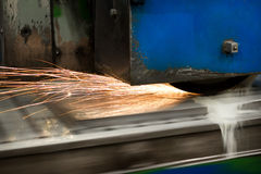 Work of an industrial surface grinding machine. Grinding of a flat metal part. Sparks fly out from under the grinding wheel. Grinding with a coolant Stock Photos