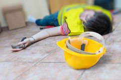 Work injury concept. Worker had an accident and is lying injured. On the floor stock photo