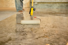 Work Lacquering concrete floors using roller for coating. In construction site Royalty Free Stock Image