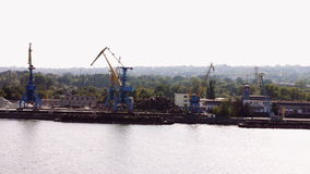 The work of a large crane in the river port. Big blue and yellow crane with bucket loads and runs a barge on the river bank. Crane turned from side to side stock video