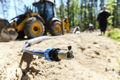 The work of a large two-wheeled tractor when laying water supply for water supply of private homes. the concept of building a coun. Try house royalty free stock photo