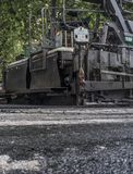 Paving applicator machine or paver at work. Work on the laying of asphalt in the city. Paving applicator machine or paver at work Royalty Free Stock Photo