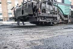 Paving applicator machine or paver at work. Work on the laying of asphalt in the city. Paving applicator machine or paver at work Royalty Free Stock Photography