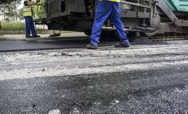 Paving applicator machine or paver with workers. Work on the laying of asphalt in the city. Paving applicator machine or paver with workers Royalty Free Stock Photo