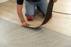 Work on laying flooring. Worker installing new vinyl tile floor. Worker installing new vinyl tile floor stock photography