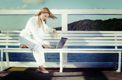 Work at leisure time. Young blonde woman with laptop on the pier. Instagram style Royalty Free Stock Photos