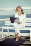 Work at leisure time. Young blonde woman with laptop on the pier Royalty Free Stock Photography