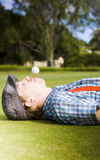 Work Life Balance. Sees A Man Take A Break To Lie Down And Relax On A Golf Course With A Tee And Golf Ball In His Mouth Balancing The Act Of Work And Play Stock Images