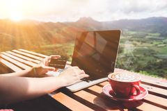 Work life balance. Business man using laptop computer and credit. Card for online financial with a cup of coffee and beautiful mountain view background Stock Images