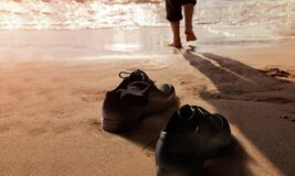 Free Work Life Balance Concept. Businessman Take Off His Working Shoes And Leave It On The Sand Beach For Walk Into The Sea On Sunny Royalty Free Stock Image - 183955736