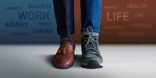 Work Life Balance Concept. Low Section of a Man Standing with Ha. Lf of Working Shoes and Casual Traveling Shoes, Blurred Text on the Wall as background royalty free stock photo