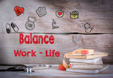 Work Life Balance Concept. Stack of books and a stethoscope on a wooden background Royalty Free Stock Photos