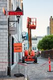 Work lift truck executes construction maintenance on Rue le Royer street and pavement closed trottoir barre sign in Montreal,. Montreal, Canada - June, 2018 royalty free stock photos