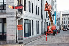 Work lift truck executes construction maintenance on Rue le Royer street and pavement closed trottoir barre sign in Montreal,. Montreal, Canada - June, 2018 stock images
