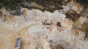 Work in the limestone quarry. Aerial footage excavator and truck work in limestone quarry. Heavy equipment in career stock footage